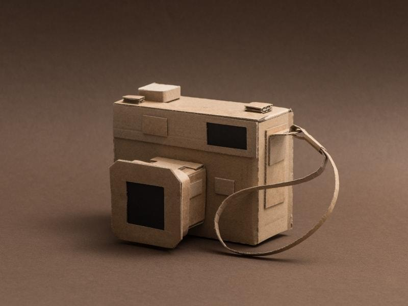 An image of a creative hand made camera out of cardboard illustrating a creative mass