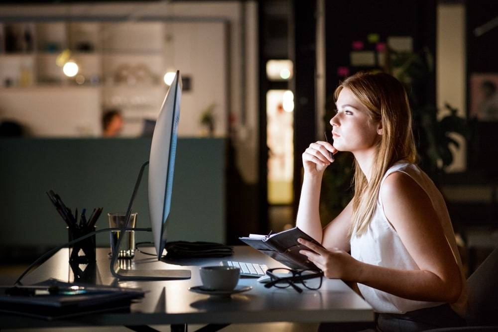 An image of a woman in office working late