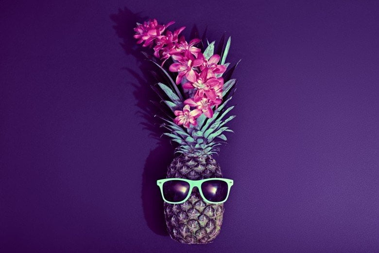 A photographs of a pineapple with sunglasses