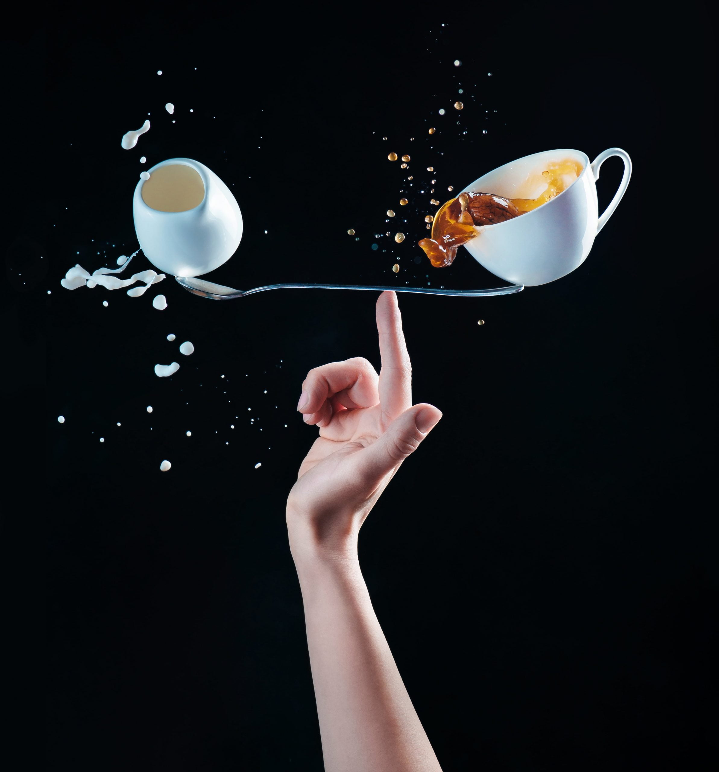An image of a small jug of milk and a cup of cofee balanced on a fork, symbolazing harmony.